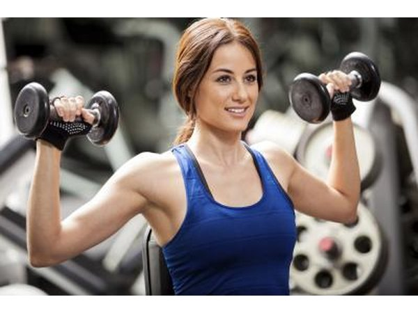 Woman lifting weights in gym.