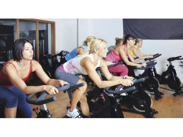 Women on stationary bikes in cycling class.