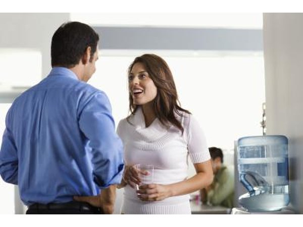 Woman talking with man at water cooler