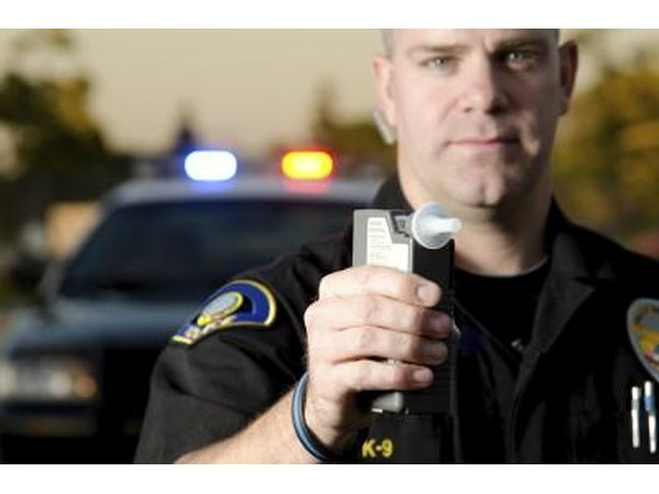 policeman holding up breathalyzer