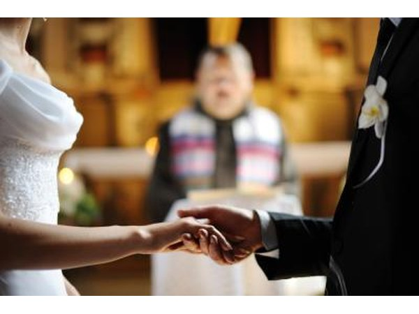 A groom holds his bride's hand during a wedding ceremony.