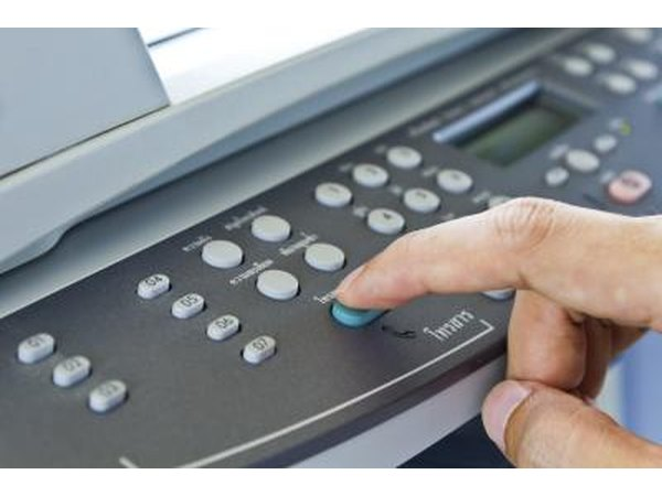 Finger pressing button on fax machine