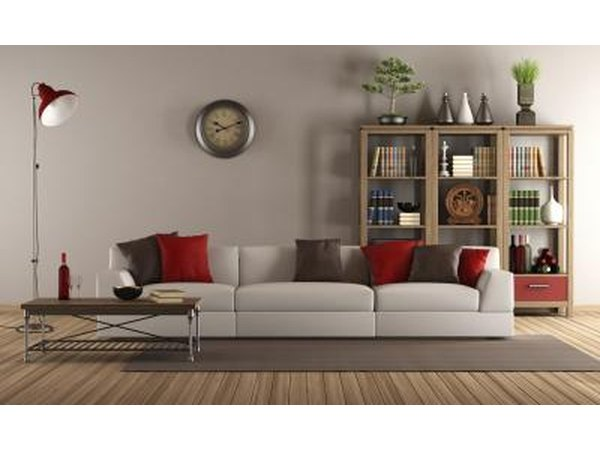 A long grey couch is mixed with a short and narrow wooden side table to offer contrast and complementary tastes.