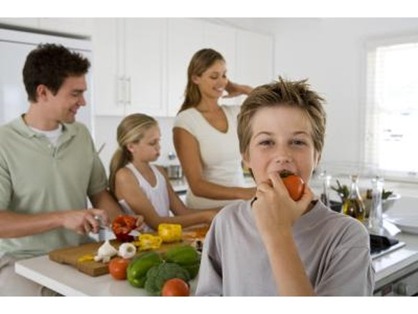 child biting into vegetable in kitchen