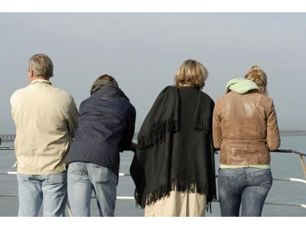 The backs of four cruise ship passengers looking over a rail.