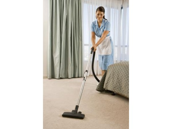 Hotel maid vacuuming