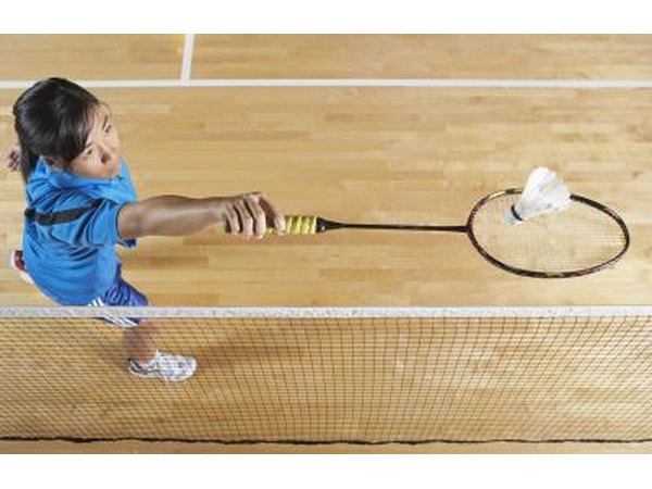 A woman uses a backhand stroke to hit the shuttle over the net.