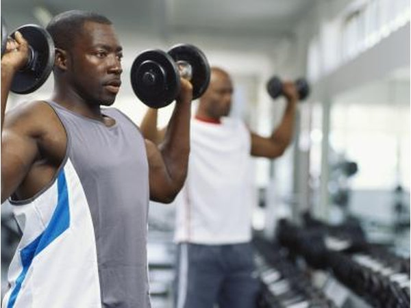 A man works out with dumbbells at the gym.