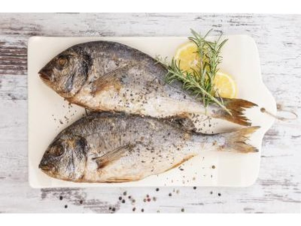 Sea bream on cutting board with lemon and rosemary