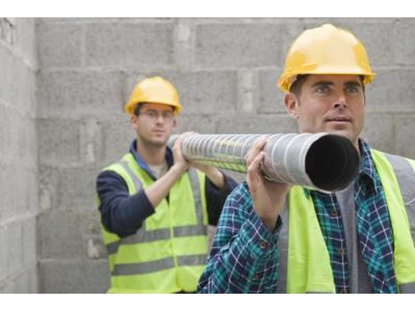 Two construction workers carrying pipe