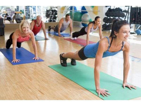 An exercise class holding plank pose in a studio.
