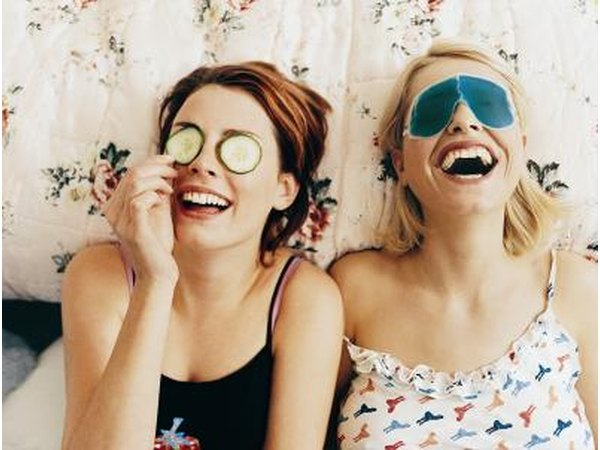 Teenage girls laughing on bed