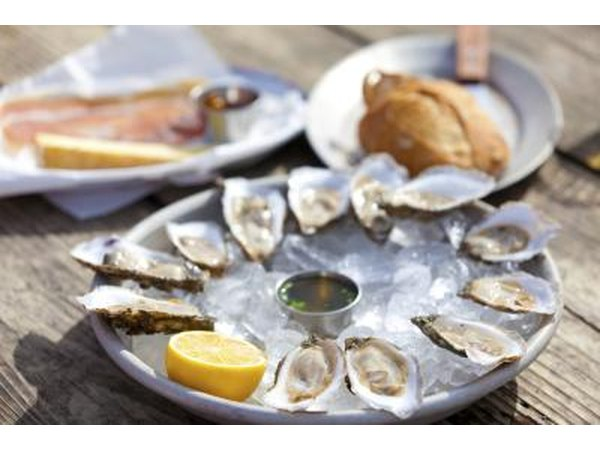 A plate of oysters with lemon on ice.