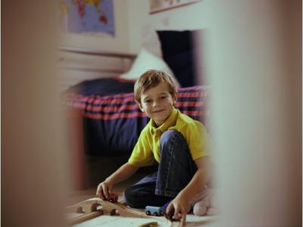 Open door with smiling young boy playing in bedroom.