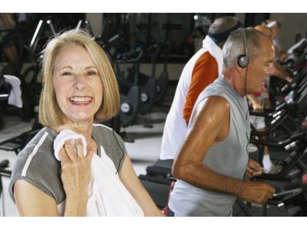 A mature woman is finishing up her workout on the treadmill.