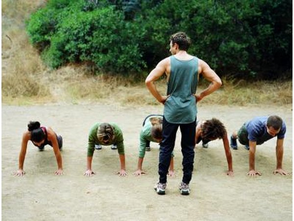 trainer and group of people doing push ups