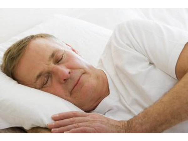 A middle aged man sleeps in a bed.