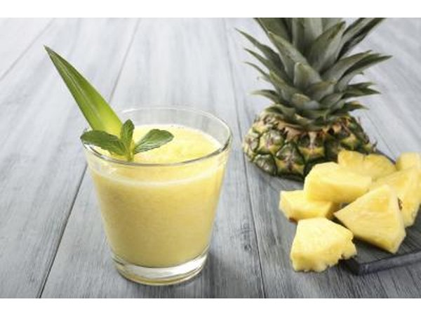 A glass of pineapple juice next to pineapple slices