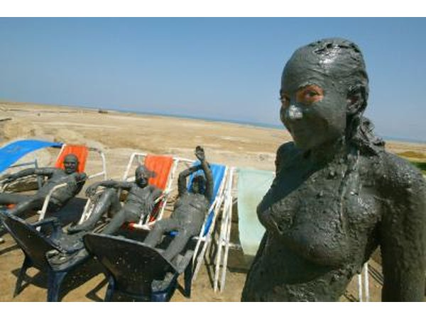 Visitors covered in mineral mud at a Dead Sea spa resort