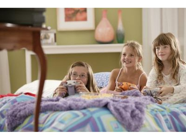 Three girls playing a video game in bed while snacking on popcorn.