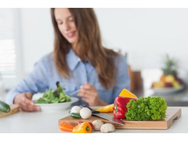 Woman eating salad with healthy vegetables in the foreground.