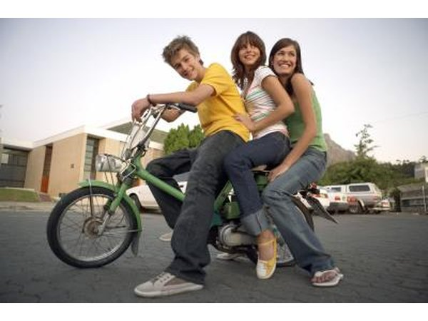 Three teenagers sit on a moped in the street.