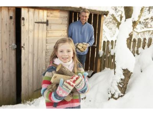 A father and daughter step outside of a firewood shed.