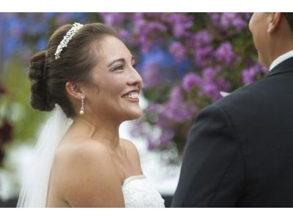 The bride smiles while listening to the groom during a wedding ceremony.