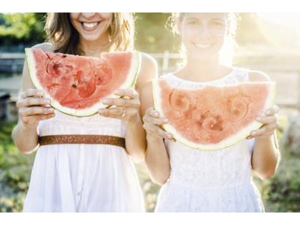 Two girls smiling and holding large slices of watermelon.