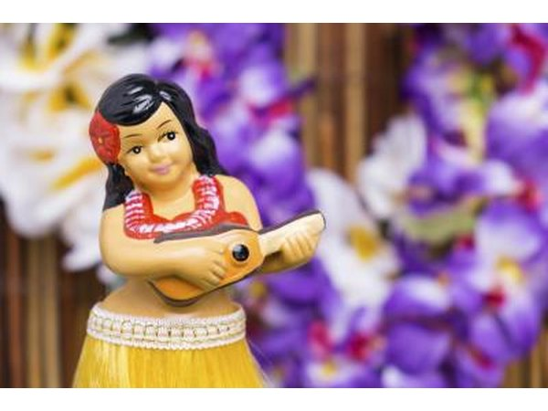 Close-up of a hula girl figurine in front of Hawaiian leis