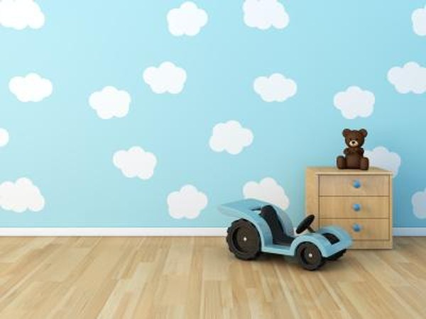 Clouds are painted onto the wall of a child's bedroom.