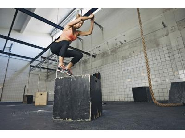A woman performs plyometrics with a jump box.