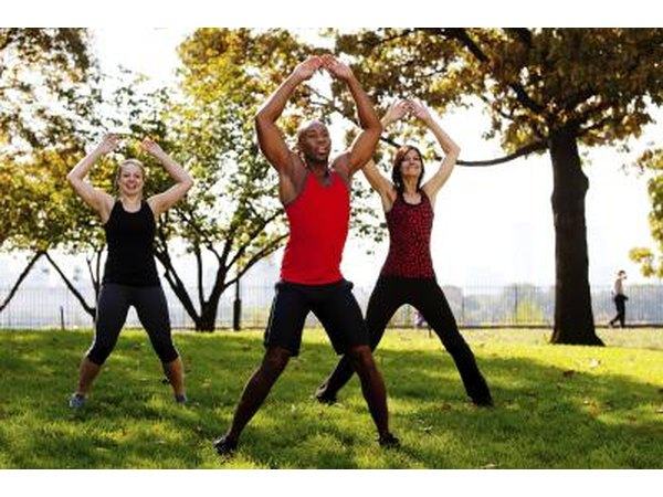 Young adults doing jumping jacks to stay active and warm