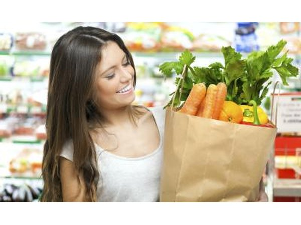 A woman is leaving the grocery store with healthy foods.