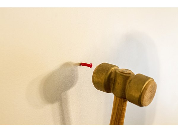 Make marks on the wall for wall anchors and hammer them into place.