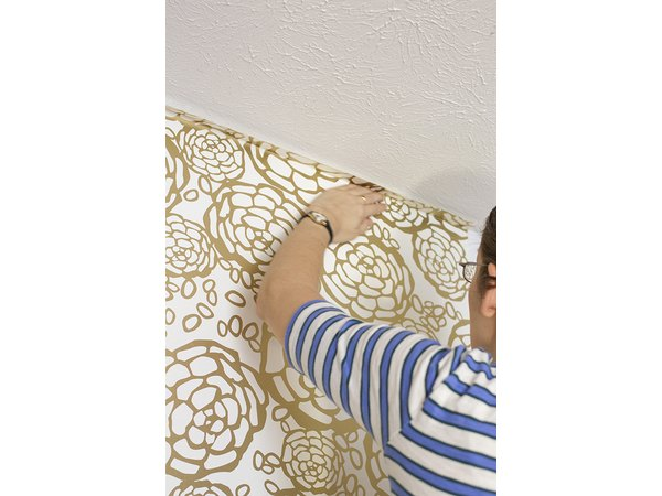 Situate the wallpaper against the wall with several inches of overhang on each end.