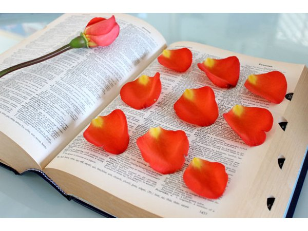 Dry rose petals by pressing them between book pages