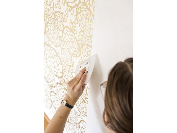 Use a squeegee to work out bubbles that may form under the wallpaper.