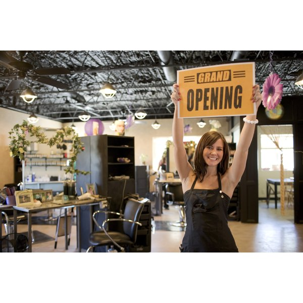 Beauty salon employee holding a grand opening sign