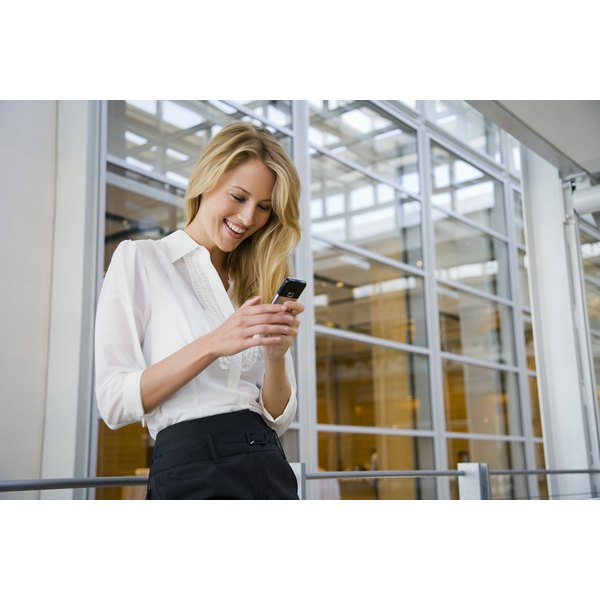 Smiling businesswoman texting