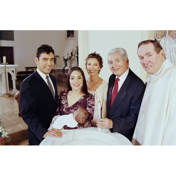 Family, baby boy and priest around baptismal font, portrait