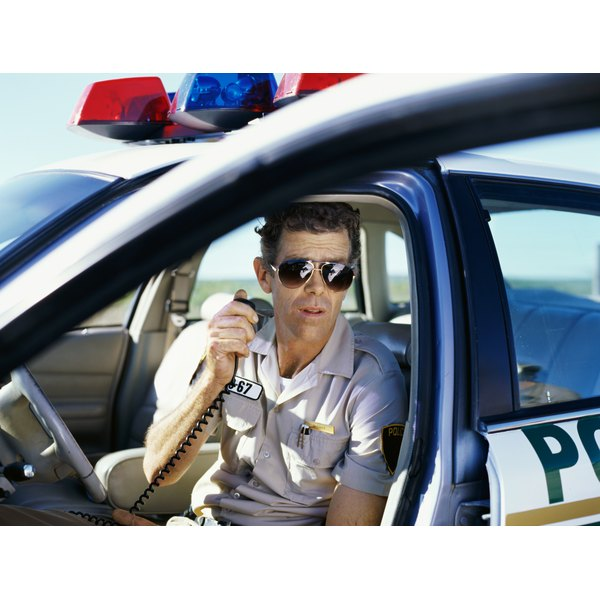 Policeman sitting in a car and using a radio