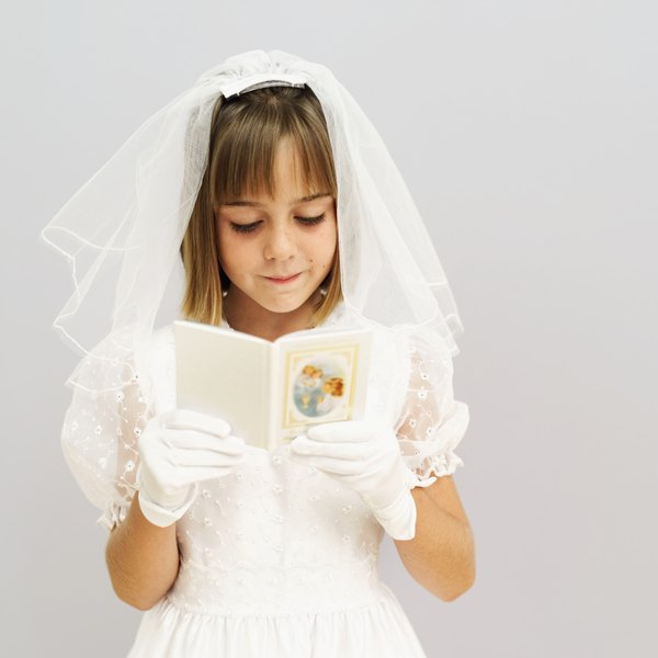 Close-up of a girl (11-13) wearing her first holy communion dress and holding prayer book