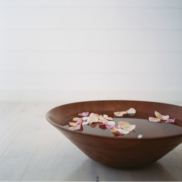 a bowl filled with water and rose petals