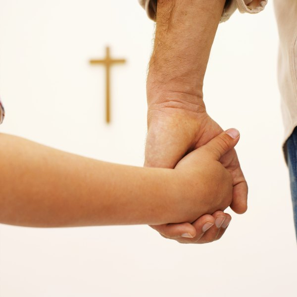 Close-up of a father and son holding hands facing a crucifix