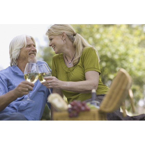 Couple having picnic and drinking wine outdoors