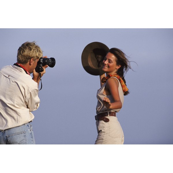 Man photographing woman holding hat