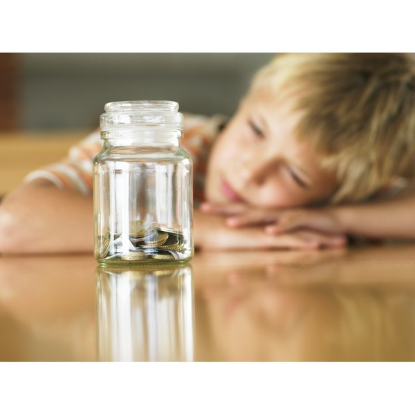 Boy (7-9) looking at coins in jar (focus on jar)