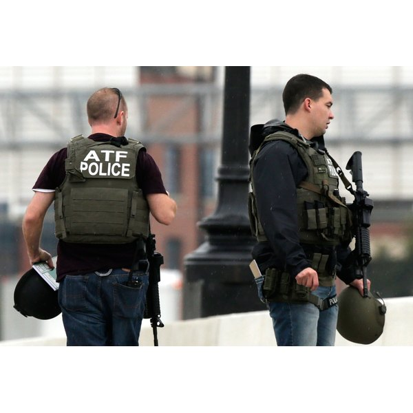 ATF agents carrying guns and wearing bulletproof vests.
