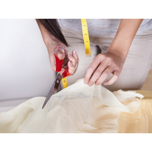 Beautiful woman cutting fabric